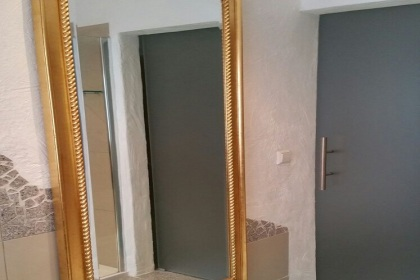 large mirror opposite the shower with sliding glass door